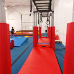 Ninja class set up, featuring swinging rings, mats, trampoline, and ropes.