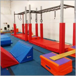 Ninja obstacle course structure at AIM Gymnastics Ajax. Set of rings, slanted mats, and a balance board.