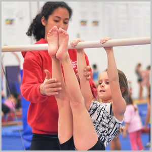 A coach helps a young female gymnast on the bars.